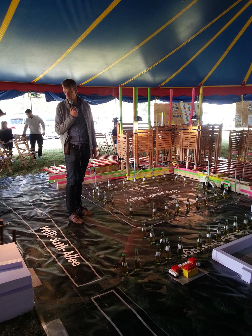 Klaus Overmeyer von Urban Catalist zeigt einen Nachbau von Chorweiler:  Die Stühle sind Hochhäuser, die Flaschen auf dem Boden sind die Bäume, der kleine Bau aus Lego ist das Cafe' Olko.