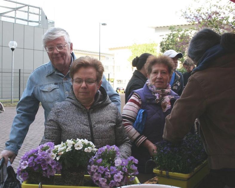 (V. L. n. R) Eheleute Sergej und Sofya Istiborovych und Diana Goldberg freuen sich über die Blumen. Sie wohnen seit 19 Jahren in dem Hochhaus und erleben zum ersten Mal solch eine Aktion eines Vermieters.
